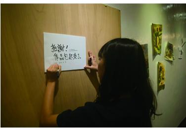 柯淮恩取下素描作品,貼上「拍謝!作品包起來了。」的通知,讓觀眾感受藝術家「正在離開」。 圖╱高中屏攝
