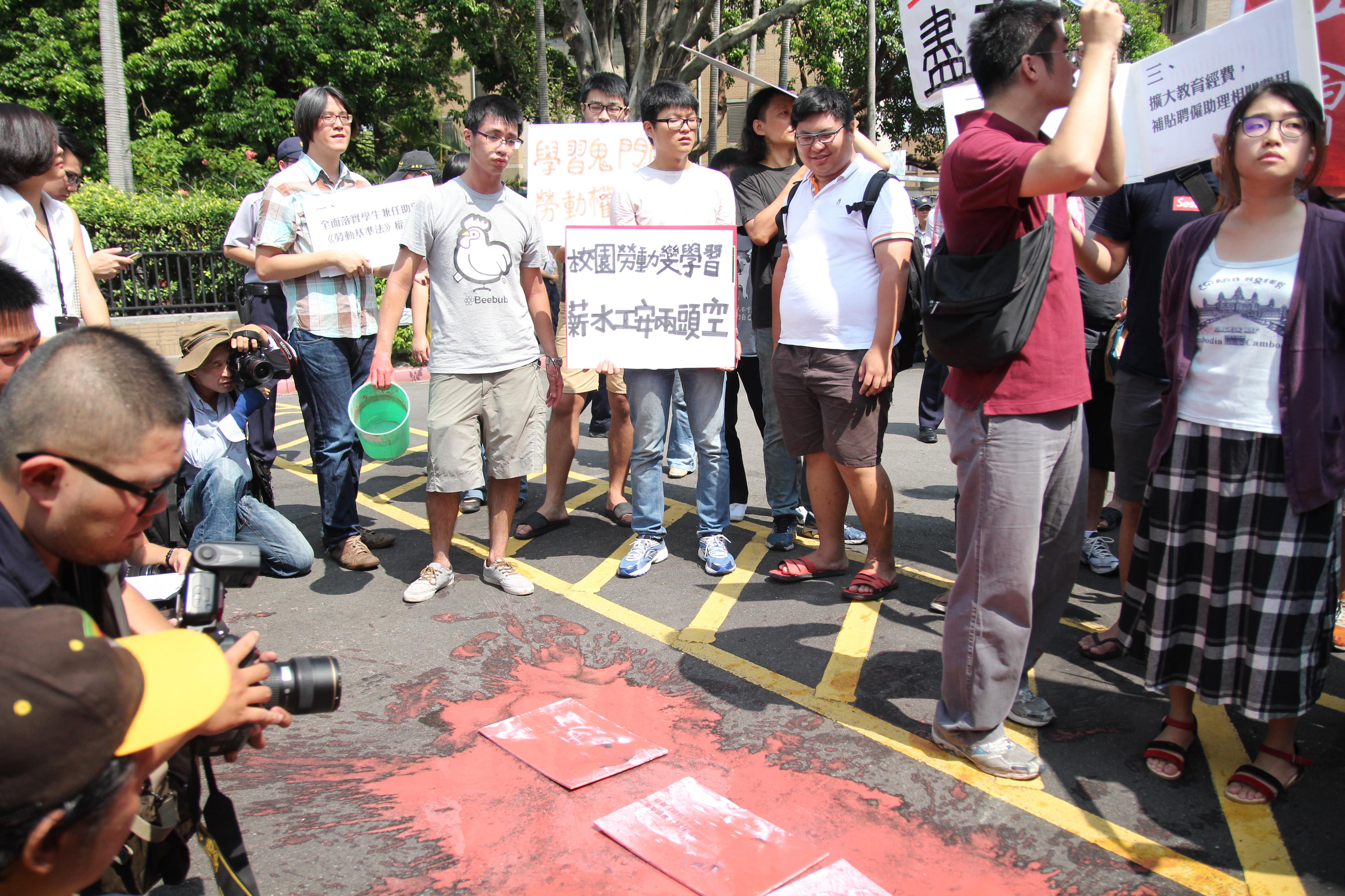 現場學生將印有個大校長照片及發言的字卡丟在地上,並淋上紅油漆,抗議校長壓榨學生助理血汗。 圖/張方慈攝