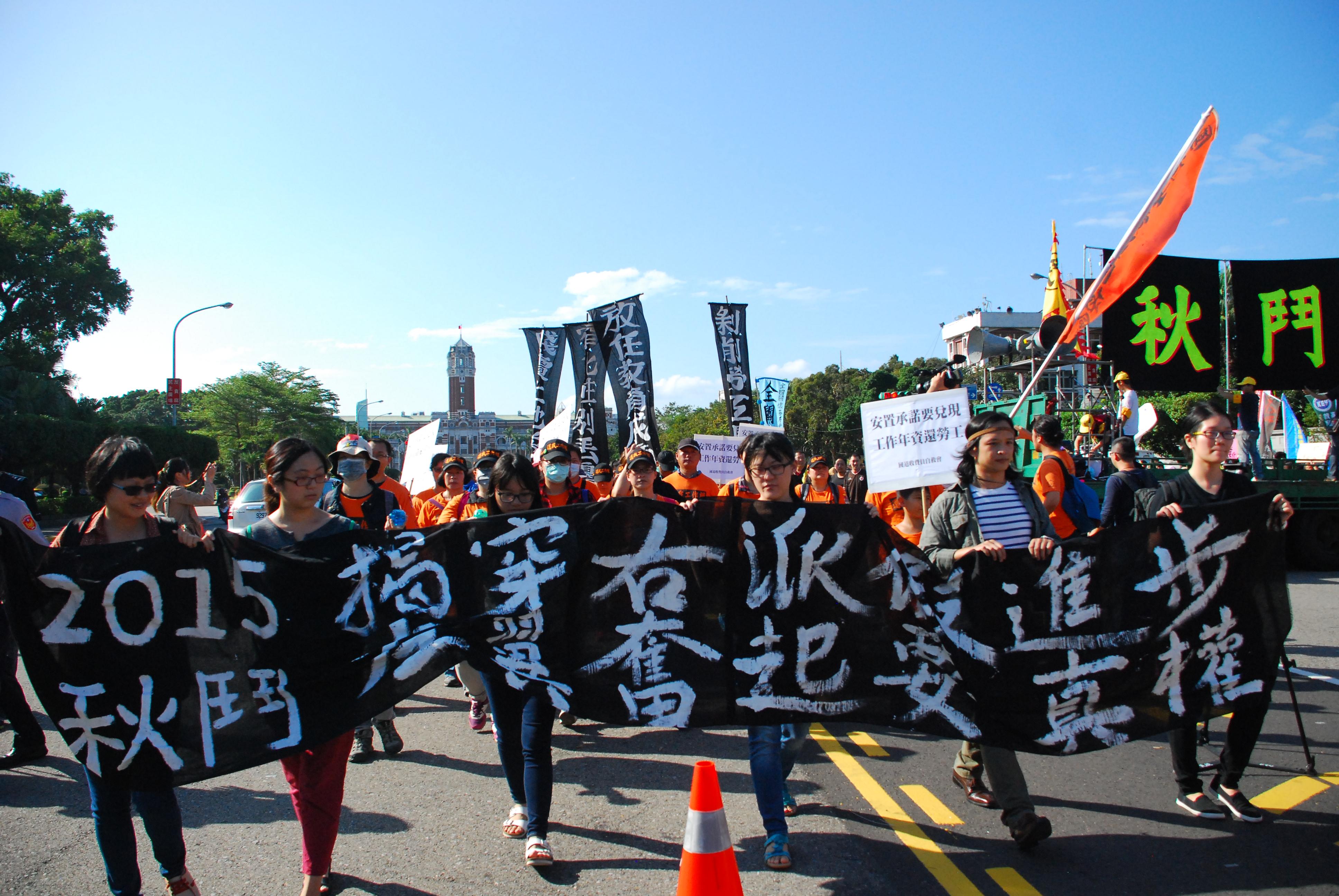 遊行隊伍從凱道出發,參加群眾拉著寫有此次秋鬥口號的布條前進。 圖/鄭晏欣攝
