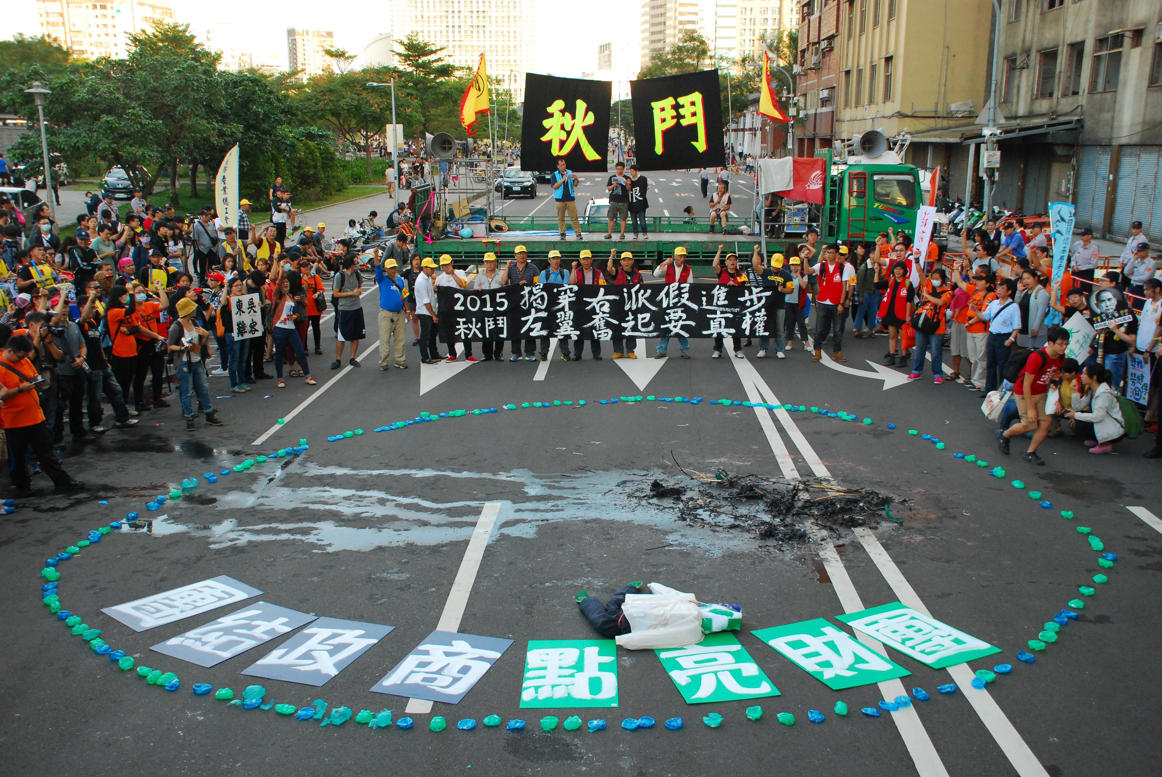 活動尾聲,群眾以踩扁的小豬圍成圓圈,諷刺藍綠兩黨總統候選人。 圖/鄭晏欣攝