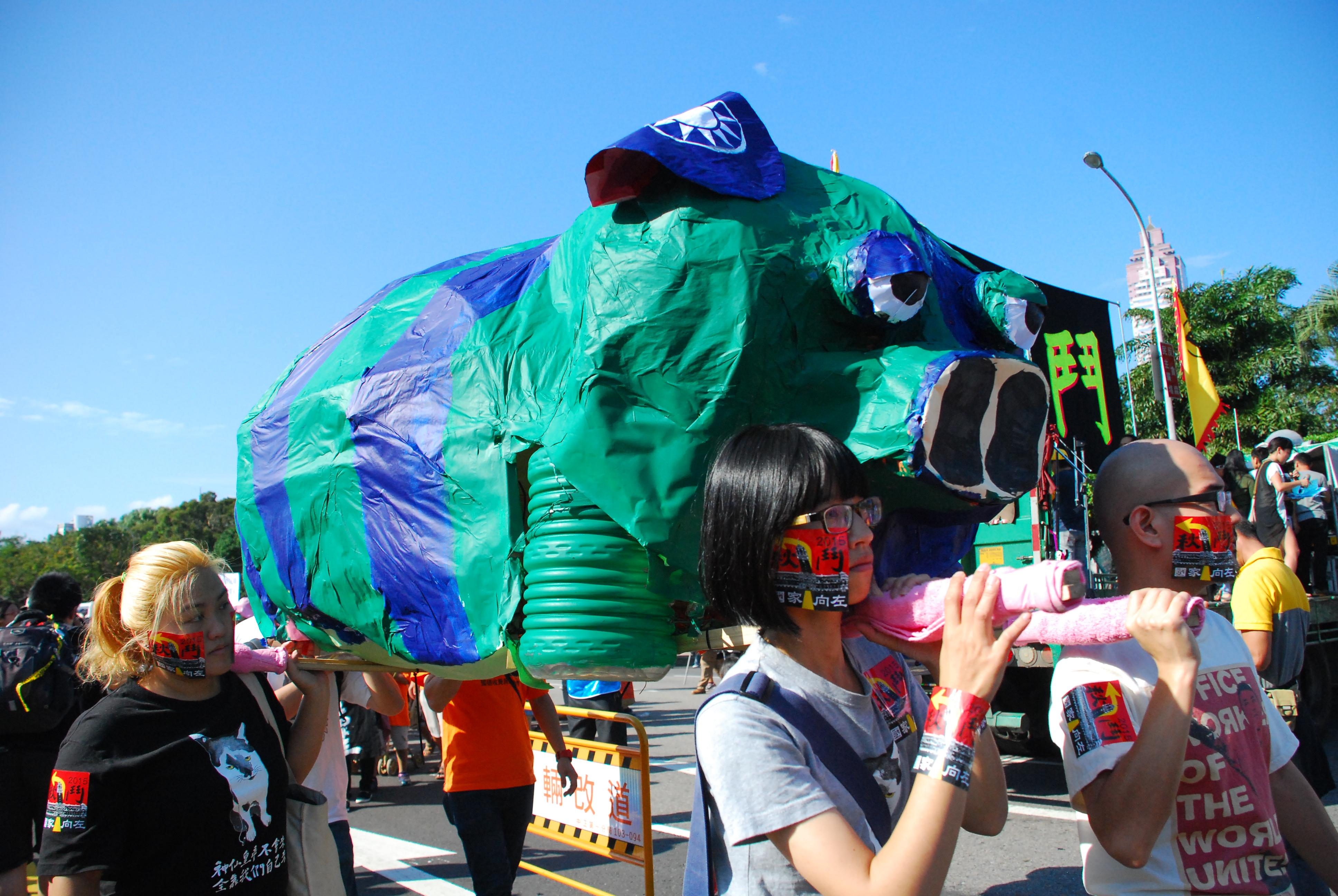 民眾扛著藍綠小豬,帶領遊行隊伍。  圖/鄭晏欣攝
