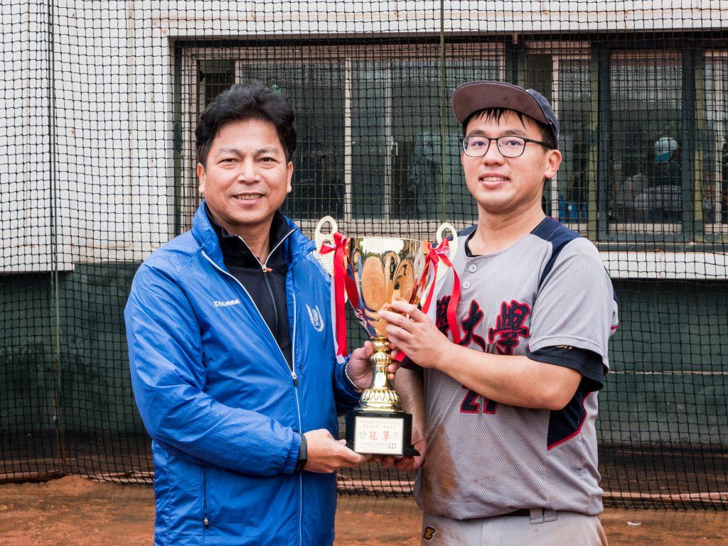 睽違十年,國立臺灣大學再度奪冠,隊長林敬倫從主辦單位手中抱回冠軍獎座。 圖/臺大男壘提供